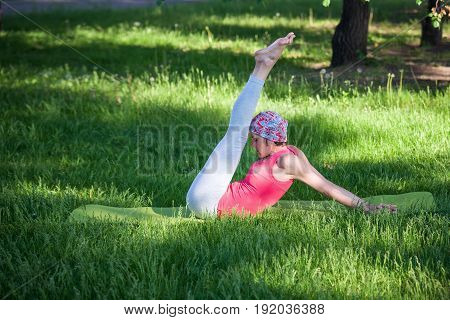 Yoga in the Park, outdoors , women's health, Yoga woman. The concept of healthy lifestyle and recreation. flexible young woman practicing yoga and gymnastics in the Park.