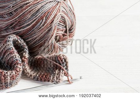 Crocheted handmade background. Knitted fabric in Gray winter tones Ball of threads and crochet hook. copy space