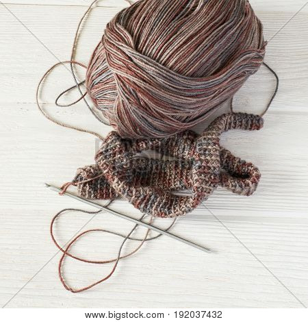 Knitted fabric in Gray winter tones Ball of threads and crochet hook.