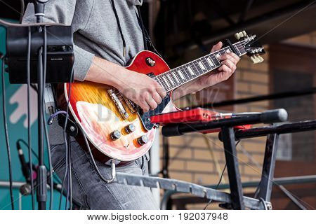 Young Male Musician Playing Electro Guitar During City Rock Fest