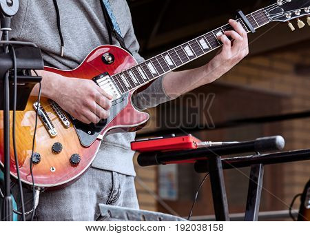 Young Guitarist Performing On Outdoor Stage During Live Concert
