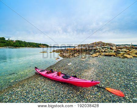 Bright red kayak on a pebble ocean beach