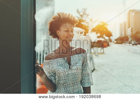 Charming young curly Brazilian girl is pushing button to use street water sprayer and get splatter of cool water on her face and body while standing on street of Rio de Janeiro on sunny summer day