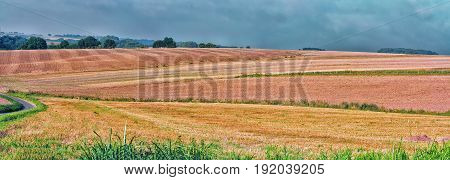 Landscape panorama of various mown grain fields.