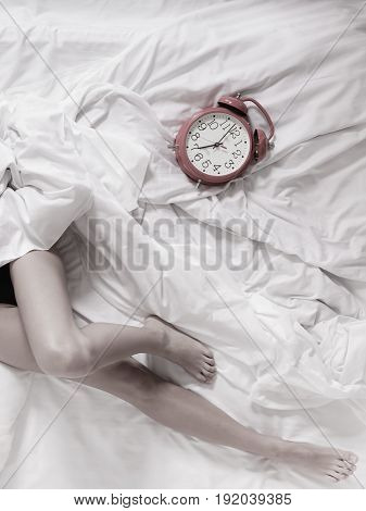 Closeup of sexy female legs with alarm clock on the bed. Woman lazy girl relaxing lazing in bedroom.