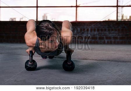 Woman athlete push ups with dumbbells on the floor. Copy space. Fitness concept