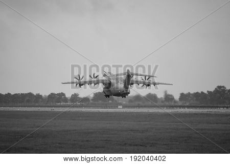 BERLIN GERMANY - JUNE 01 2016: Demonstration flight at rainy day of the military transport aircraft Airbus A400M Atlas. Black and white. Exhibition ILA Berlin Air Show 2016