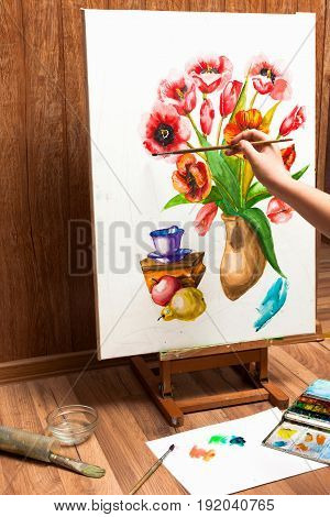 Painter drawing watercolor flowers. Unrecognizable artist's hand paints bouquet picture . Drawing lessons, art school, young artist concept