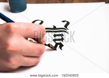Process of calligraphy lettering. Background. Unrecognizable artist's hand drawn word inspire with ink on white paper. Drawing lessons, art school, creativity concept