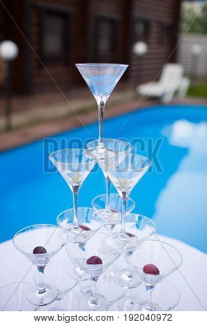 the glasses are to each other on the background of the pool