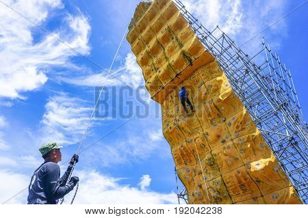 Labuan,Malaysia-May 21,2017:Adventure group of climber with safety equipment climb on climbing wall in Labuan,Malaysia.It is an activity in which participants climb up,down or across artificial rock walls