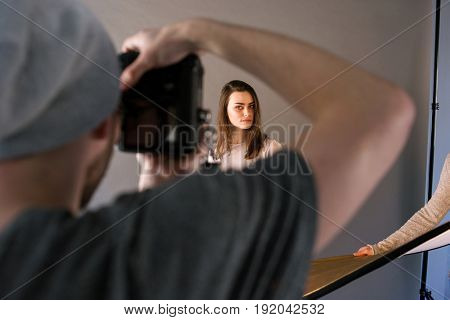 Backstage of professional studio photo session . Unrecognizable man taking shot of female model, and assistant helps him. Photo school, lookbook, fashion blogger concept