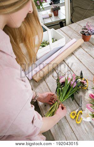 Woman making tulip bouquet top view. Unrecognizable florist make floristry assemble in workshop on wooden background