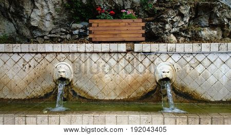 The famous fountain with the flowing water from the lions ' mouths in the village of Spili in Crete