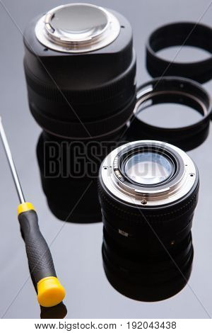 Precision optical dslr lens service, adjustment and alignment. Camera lens repair set in photo engineer workspace. Maintenance support of photographic photo camera lenses