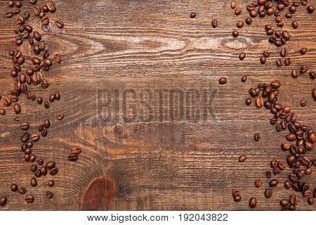 Roasted coffee beans frame on wooden background. Closeup of seeds on dark brown table. Top view.
