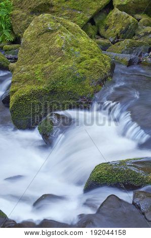 Large mossy rocks with rushing flowing waterfall