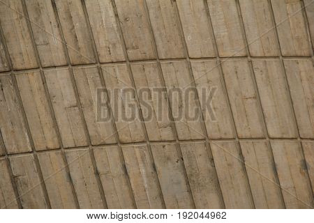Horizontal shot of stone background with heavy carvings going in horizontal and vertical lines.