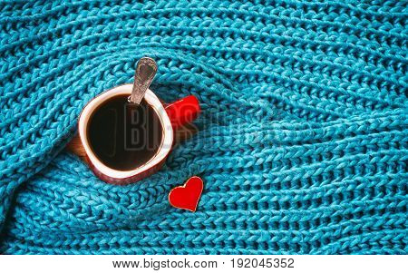 Turquoise knitted woolen scarf red mug with coffee heart valentine day composition top view