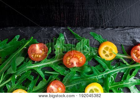 Fresh Arugula Salad With Kumquat And Tomato Cherry On Slate Plate. Top View. Healthy Food. Diet.