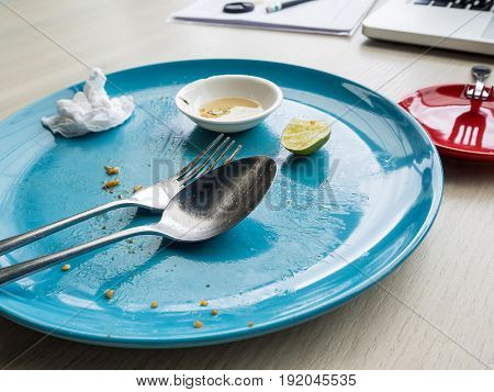 Dirty and empty dish with spoon and fork after meal finish