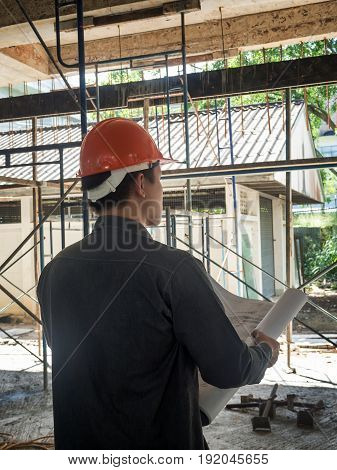 Back of foreman with blueprint on construction site