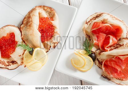 Set of luxury pancakes with seafood. Top view on white plates. Russian traditional salty crepes with seafood. Shrove tuesday holiday food
