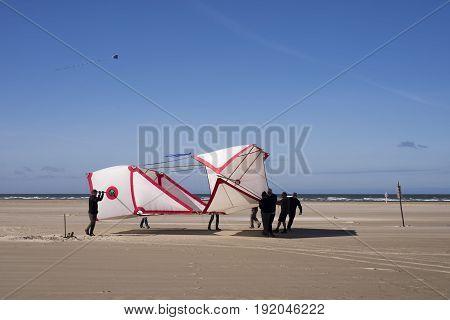 FANOE DENMARK JUNE 17 2017: Early start at the dragon festival where 8 men carry a huge kite with the North Sea in the background on Fanoe beach. Fanoe Kite Fliers Meeting June 2017.