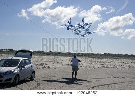 FANOE DENMARK JUNE 17 2017: Early start at the dragon festival where a man sets his kite up on Fanoe beach. Fanoe Kite Fliers Meeting June 2017.