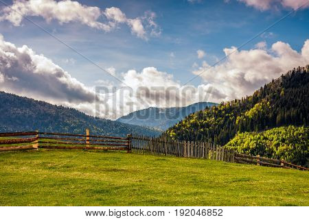 Fence Through The Grassy Meadow In Mountains