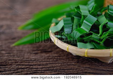 portion cut pandan leaves in bamboo basket and on wooden table