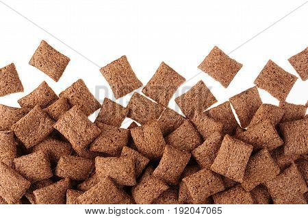 Chocolate pads corn flakes isolated with copy space background. Cereals texture.