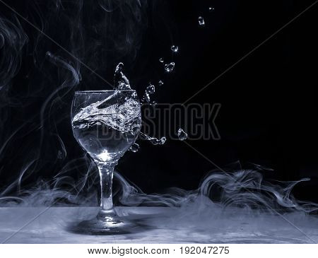 Splash of water from a glass on a smoke background