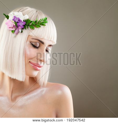 Blonde Beauty. Perfect Model Woman with Healthy Skin Bob Hairstyle and Spring Flowers on Background with Copyspace. Facial Treatment and Cosmetology