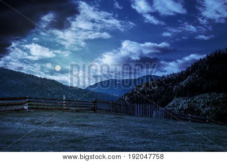 Fence Through The Grassy Meadow In Mountains At Night In Full Moon Light