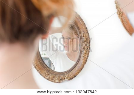 Girl preens in front of mirror, beautiful face looks up in a mirror . Woman primp her hair. Pretty girl examines a mirror