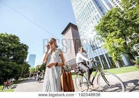 FRANKFURT, GERMANY - May 16, 2017: Businesswoman with phone and businessman on the bicycle in the modern district in Frankfurt city