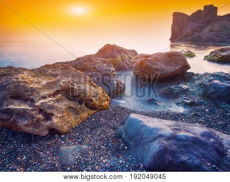 Seascape during sunset. Beautiful natural seascape at long exposure. Stones at foreground
