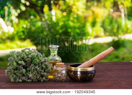 Aromatic thyme essential oils and singing bowl. Spa and relaxation. Herbs and oils on a green blurred background.