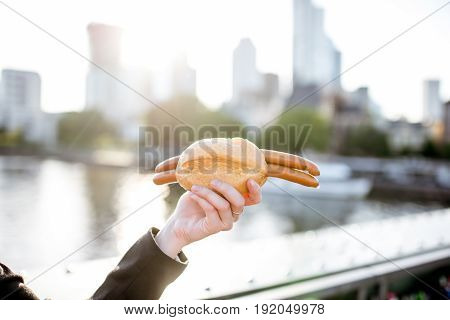 Traditional frankfurt sausages with bread in the hand on the Frankfurt city background