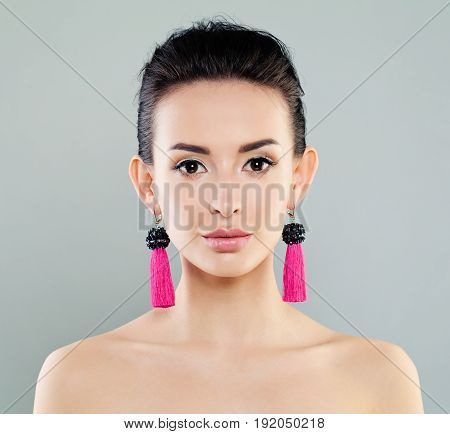 Beautiful Woman with Pink Earrings on gray