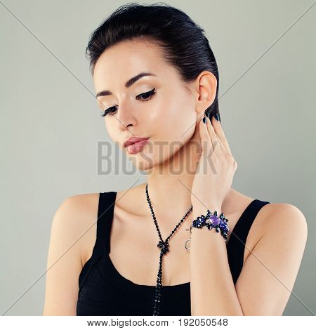 Perfect Woman with Makeup and Jewelry on gray