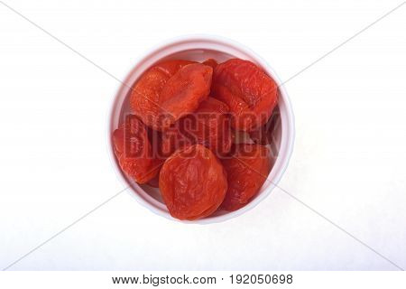 Delicious dried organic apricots on bowl isolated over white background