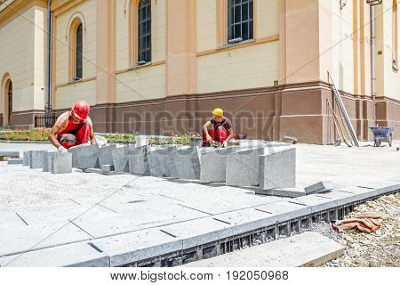 Zrenjanin Vojvodina Serbia - June 19 2015: Team of masons is fitting flagstone they making footpath paving large street.