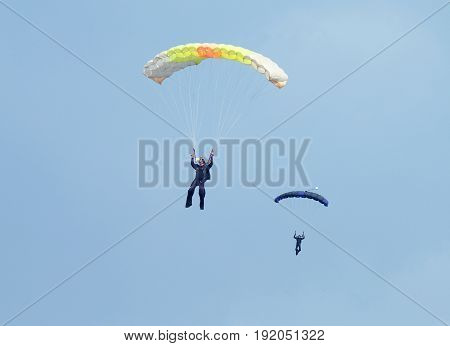 Two Skydivers With Colourful Chutes Approaching Landing Area In Queue.