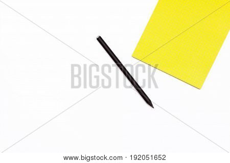 Black Pencil And A Yellow Notepad On A White Background. Minimal Concept Workspace.