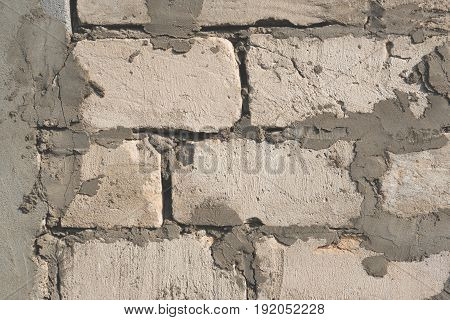 The background of cement and blocks on the wall grey plain textured with cracks close up .