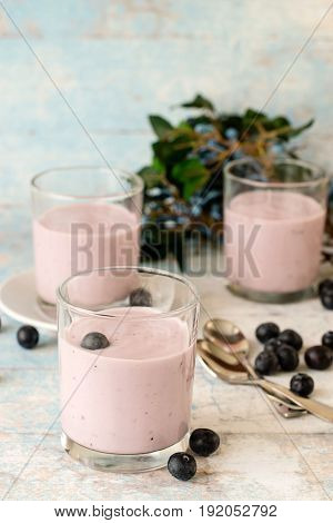 Blueberry dessert. Yogurt in a glass and fresh berries blueberries on a blue wooden table.