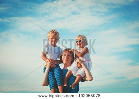 happy father with two kids on shoulders at blue sky