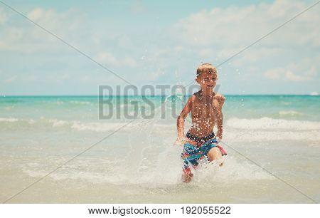 happy boy run play with waves on tropical beach